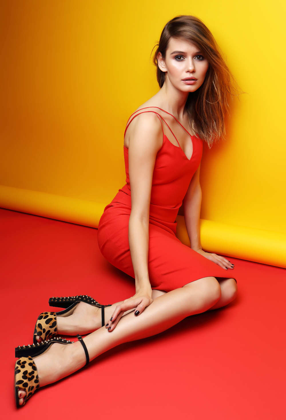 Portrait of brunette woman wearing red mini dress with leopard print shoes over yellow and red background.
