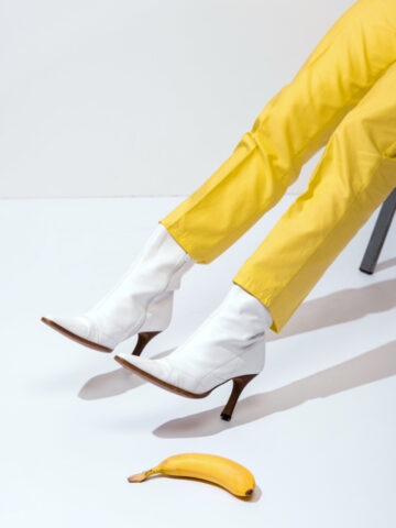 Image insinuating Slippery Shoes in post about how to make shoes less slippery with woman's legs wearing white boots and yellow pants near banana laying on ground.
