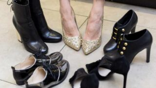 Woman's feet wearing gold sparkle heels surrounded by black shoes.