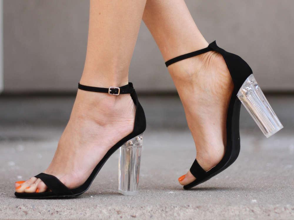 Woman Wearing Lucite Heels on Black Sandals- Different Types of Heels   ShoeTease