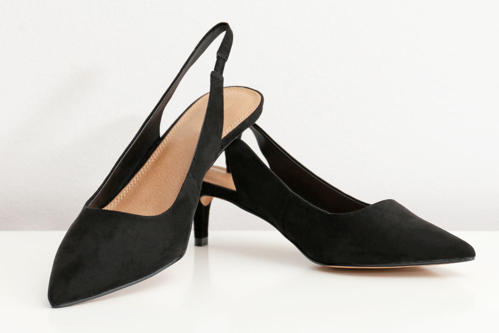 Pair of women's slick back heels shoes against white background.