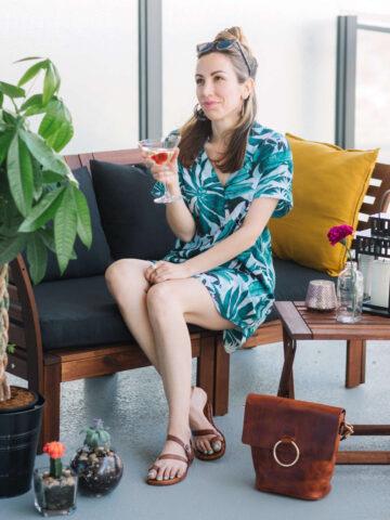 Woman sitting on patio in summer dress wearing Australian shoe brands Wittner sandals.