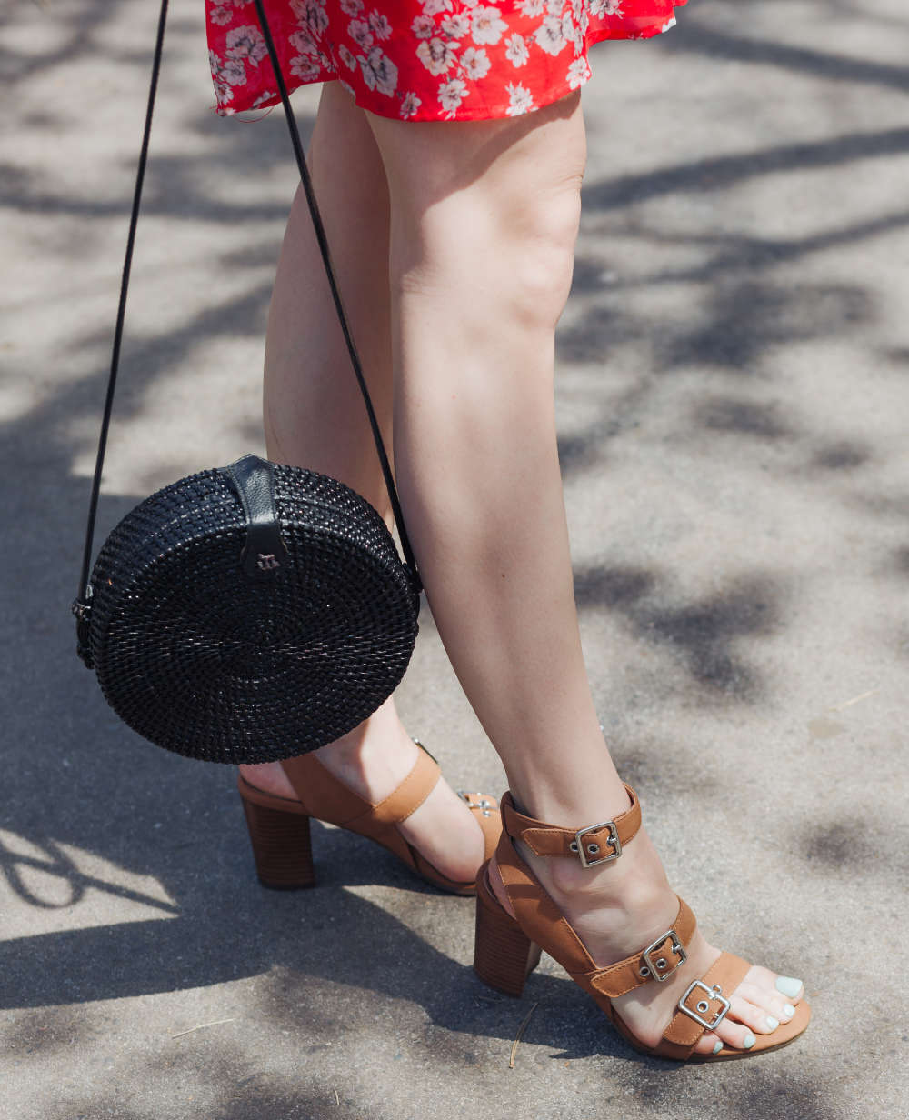 Lady wearing Brown sandals holding round purse with red summer dress.