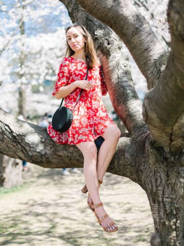 Lady sitting in tree wearing floral short dress with high heel shoes, to illustrate post on shoes to wear with dresses.