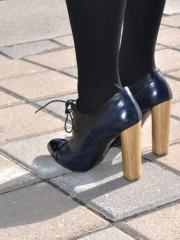 Post about the best shoe glue illustrated with image of woman wearing wooden heeled oxfords standing on bricks.