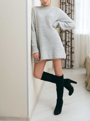 Girl wearing beige sweater dress with boots that are black and knee high, leaning against bedroom wall.