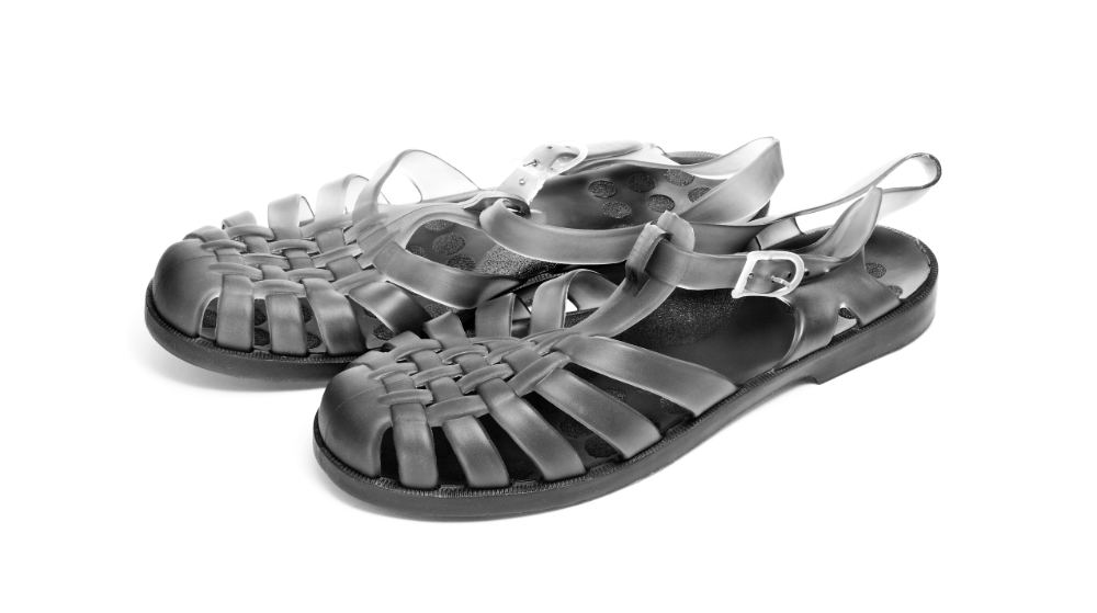A pair of black jelly sandals on a white background.