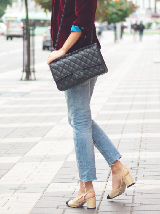 What shoes to wear with straight leg jeans with Side view of woman in jeans and jacket on street with bag.
